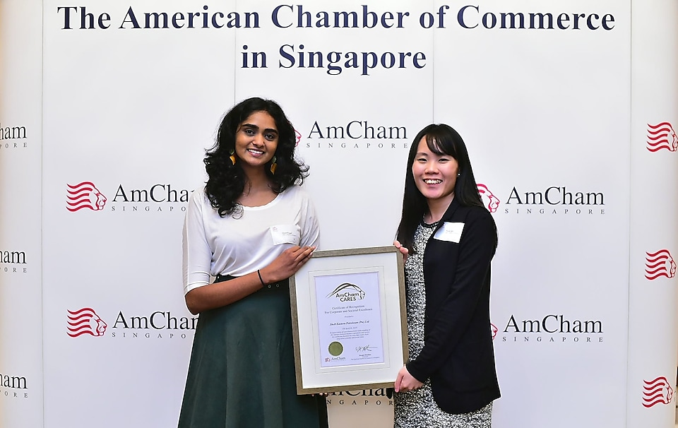 (From left to right) External Relations Advisors Niyati Pingali (left) and Nicole Pauh (right) receive the AmCham Cares for Corporate and Societal Excellence award on Shell's behalf