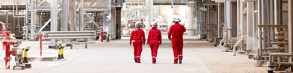 Three engineers walking onsite at a refinery