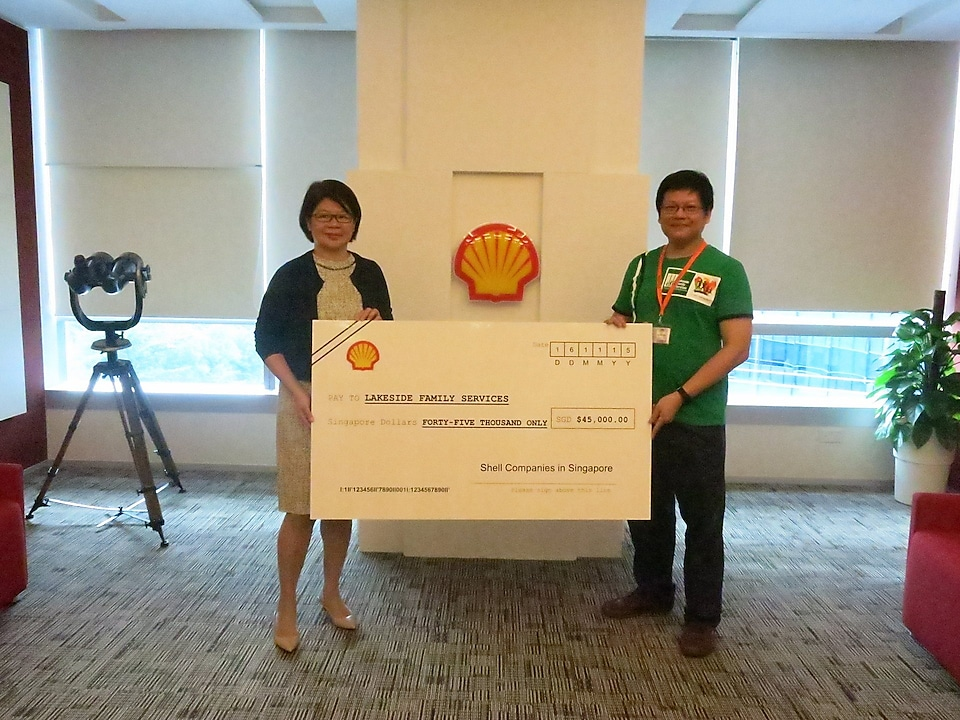 (From left) Shell Singapore chairperson Goh Swee Chen presents the cheque to Lakeside Family Services Executive Director Teo Tee Loon