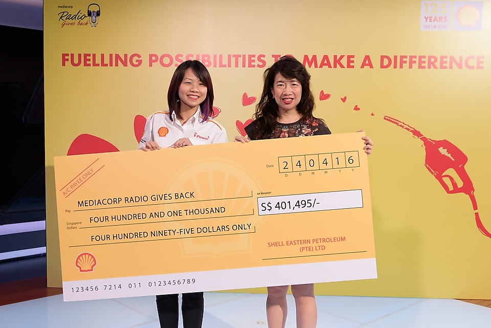 A Shell Singapore representative presents a cheque of $401,495 in donations to Ms Debra Soon, Chairperson, Mediacorp's Radio 80 Committee
