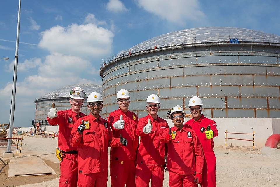 six workers showing thumbs up with two large crude oil tanks in their background