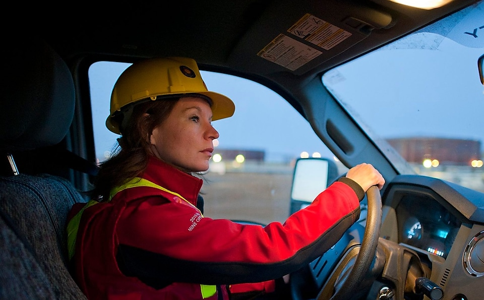 A lady wearing safety equipment driving a vehicle
